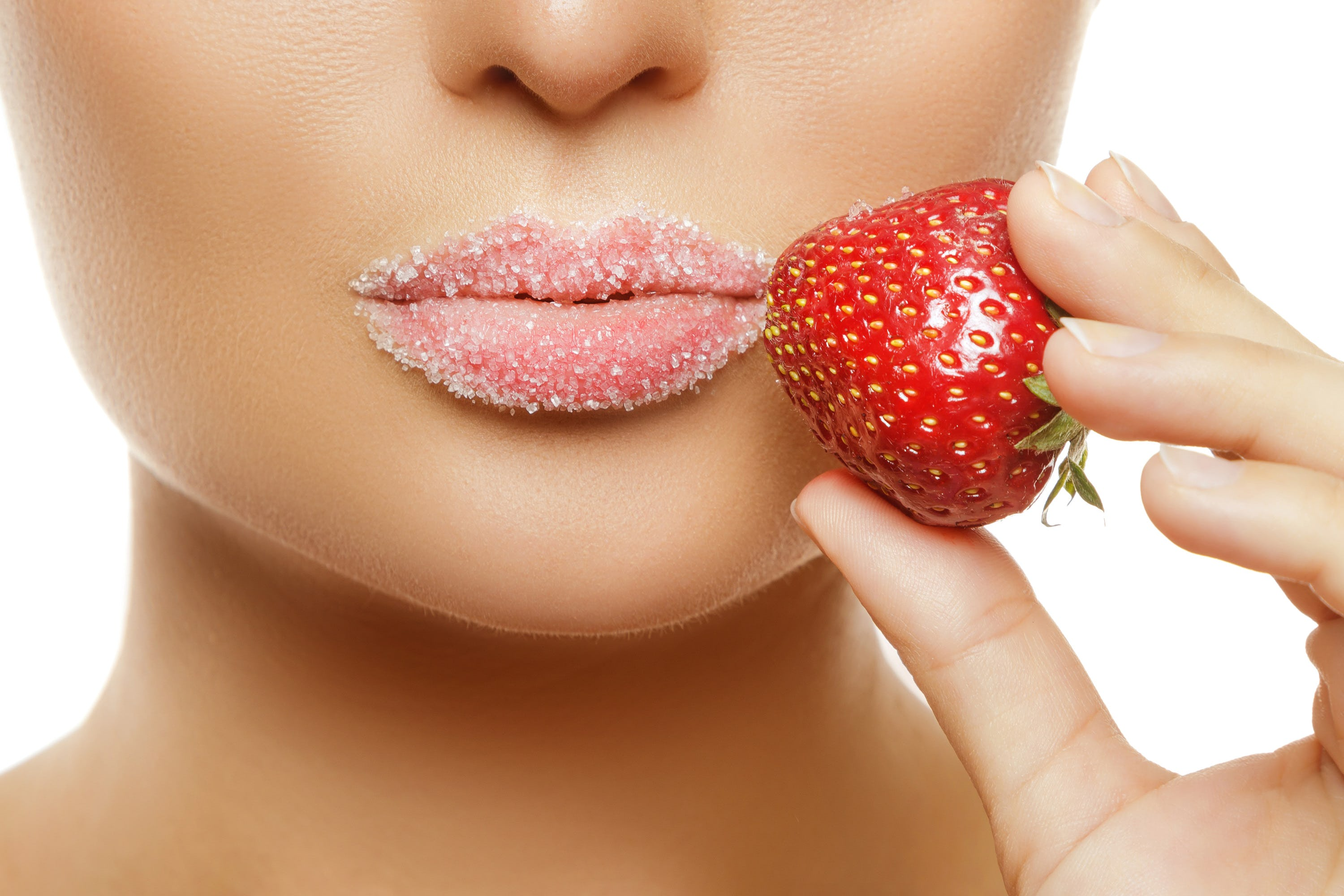 Close-up of lips with sugar and a strawberry