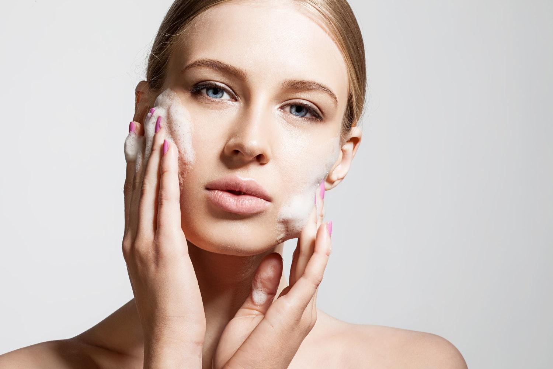 Frau reinigt ihr Gesicht mit Schaum
