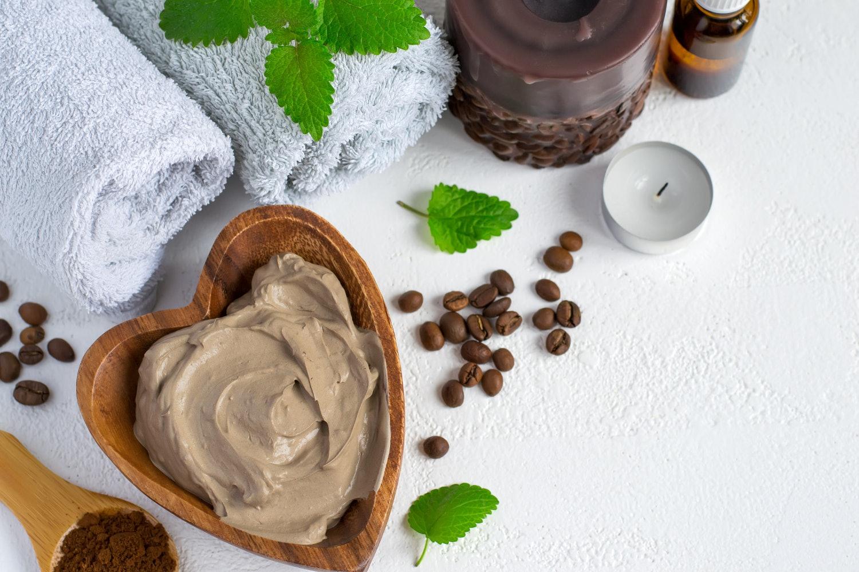 Spa-Setting mit kosmetischer Tonmaske für den Körper, Handtuch Ätherisches Öl und Kaffeebohnen