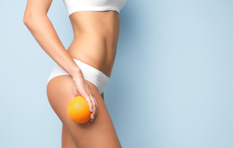 Junge Frau hält eine Orange