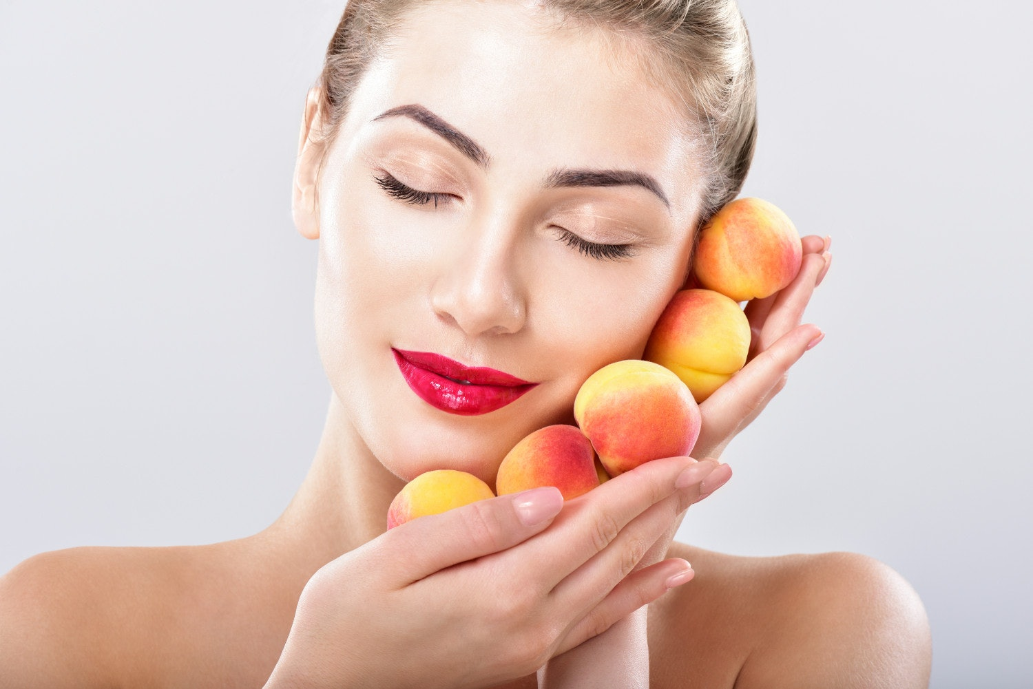 Beautiful woman holding a juicy apricot