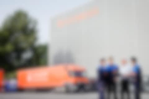 Oranger LKW und eine Gruppe von vier Personen for dem Hochregallager